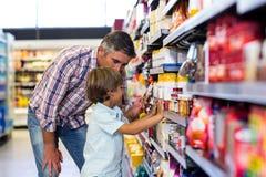Cute child choosing food from shelf Royalty Free Stock Photos