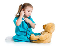 Cute child with clothes of doctor examining teddy bear toy. Adorable child with clothes of doctor examining teddy bear toy over white Stock Images