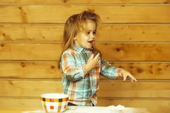 Cute child cooking with dough, flour and bowl on wood royalty free stock image