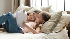 Cute child daughter holding book reading to mom in bed. Cute preschool child daughter holding book reading fairy tale to mom lying in bed together, happy mother royalty free stock image