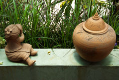 Cute child doll and pot in garden Royalty Free Stock Photography