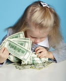 Cute child with dollars on table Royalty Free Stock Photos