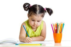 Cute child drawing with colorful crayons Stock Photos