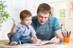 Cute child drawing with colourful pencils. Adorable kid child boy drawing with colorful pencils Stock Image