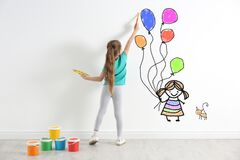 Cute child drawing girl with balloons and cat on wall indoors