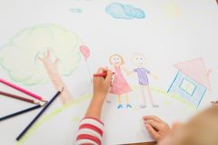 Cute child draws house and family on paper. Top view Royalty Free Stock Images