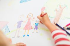 Cute child draws house and family on paper. Top view Stock Photography
