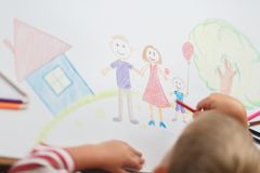 Cute child draws house and family on paper. Top view Royalty Free Stock Photo