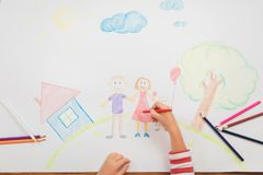 Cute child draws house and family on paper. Top view Stock Photo