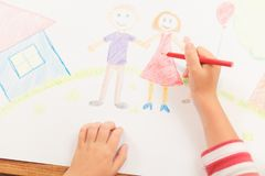 Cute child draws house and family on paper. Top view Stock Image