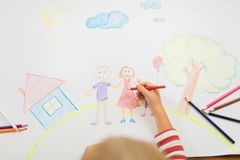 Cute child draws house and family on paper. Top view Royalty Free Stock Photography