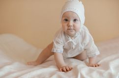 Cute child dressed in white crowling in the bed Royalty Free Stock Images