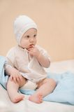 Cute child dressed in white sits on the bed thinki Royalty Free Stock Photos