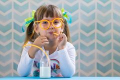 Cute child drinking milk with funny glasses straw. Growing up. Cute girl kid drinking milk with funny glasses straw on blue background. Growing up concept royalty free stock image
