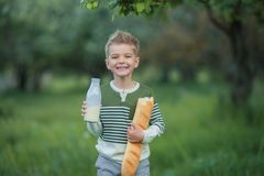 Cute child drinking milk outdoors. Cheerful boy on the picnic royalty free stock image
