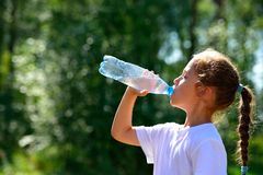 Cute child drinking water from a bottle Royalty Free Stock Image