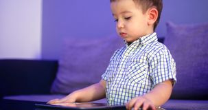 Cute Child Entertaining With Tablet. Little Boy Spending Leisure Time Playing Mobile Game in the and Crushes the Bright. Screen With Her Hand. Concept stock video
