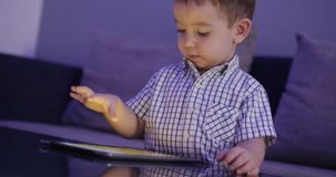 Cute Child Entertaining With Tablet. Little Boy Spending Leisure Time Playing Mobile Game in the and Crushes the Bright. Screen With Her Hand. Concept of:Happy stock video footage