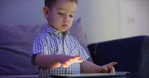 Cute Child Entertaining With Tablet. Little Boy Spending Leisure Time Playing Mobile Game in the and Crushes the Bright. Screen With Her Hand. Concept of:Happy stock footage