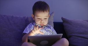 Cute Child Entertaining With Tablet. Little Boy Spending Leisure Time Playing Mobile Game in the and Crushes the Bright. Screen With Her Hand. Concept of:Happy stock video