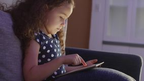 Cute Child Entertaining With Tablet. Little Girl Spending Leisure Time Playing Mobile Game in the and Crushes the Bright. Screen With Her Hand. Concept of:Happy stock video