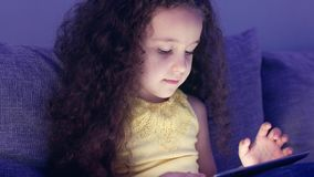 Cute child entertaining with tablet. Little girl spending leisure time playing mobile game in the and crushes the bright. Screen with her hand. Concept of stock video footage