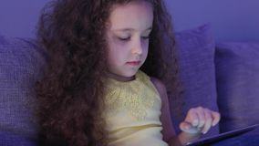 Cute Child Entertaining With Tablet. Little Girl Spending Leisure Time Playing Mobile Game in the and Crushes the Bright. Screen With Her Hand. Concept of:Happy stock footage