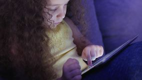 Cute child entertaining with tablet. Little girl spending leisure time playing mobile game in the and crushes the bright. Screen with her hand. Concept of:happy stock video footage