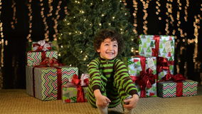 Cute Child Excitedly Sits in Front of Christmas Tree stock footage