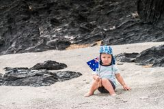 Cute child with flag of Australia. Cute child sitting on the beach with Australian flag on Australia day Royalty Free Stock Image