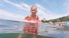 Cute child girl on air mattress in sea. Family vacation concept.