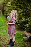 Cute child girl with basket of bluebells in spring garden Royalty Free Stock Photos