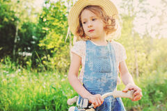 Cute child girl with bicycle on summer sunny road Stock Photos