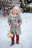 Cute child girl with bird feeder and seeds in winter snowy garden Stock Images