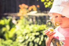 Cute child girl blowing soap bubble in summer park in sunny day with sunlight. Cute child girl blowing soap bubble in summer park in sunny day with bright Royalty Free Stock Images