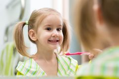 Cute child girl brushing teeth and looking in mirror in bathroom royalty free stock image