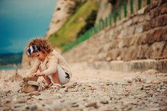Cute child girl building stone tower on the beach Stock Image