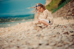 Cute child girl building stone tower on the beach Stock Photos