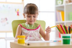 Cute child girl cheerfully spending time using pencils while drawing in playschool stock images