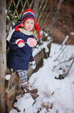 Cute child girl in christmas hat with candy in winter snowy garden Royalty Free Stock Photo