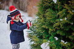 Cute child girl in christmas knitted hat decorating tree in winter snowy garden Royalty Free Stock Image