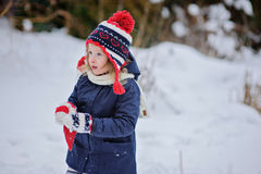 Cute child girl in christmas knitted hat walking in winter snowy garden Royalty Free Stock Photo