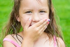 Cute child girl covering her mouth don`t speak can`t talk, but s. Cute child girl covering her mouth don`t speak stopped talking in surprise smiling over funny stock images