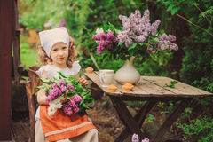 Cute child girl on cozy outdoor tea party in spring garden with bouquet of lilacs. Vintage style dress stock image