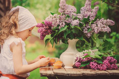 Cute child girl on cozy outdoor tea party in spring garden with bouquet of lilacs Stock Photo