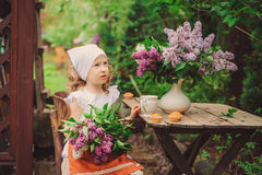 Cute child girl on cozy outdoor tea party in spring garden with bouquet of lilacs Royalty Free Stock Photo
