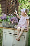 Cute child girl cutting lilacs in spring garden Royalty Free Stock Photo