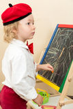 Cute child girl drawing chalk on easel in suit of artist in preschool Royalty Free Stock Photo