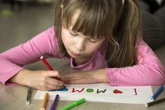 Cute child girl drawing with colorful crayons I love Mom on white paper. Art education, creativity concept royalty free stock images
