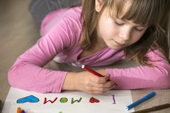 Cute child girl drawing with colorful crayons I love Mom on white paper. Art education, creativity concept.  stock photo